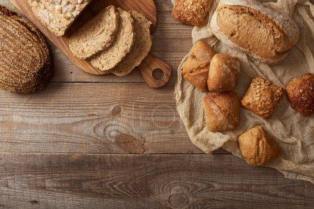 Photo pour Vue de dessus des tranches de pain fraîches cuites au four sur la planche à découper et des petits pains sur le tissu sur la table en bois - image libre de droit