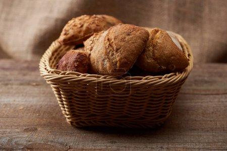 Photo pour Petits pains frais cuits au four dans un panier en osier sur une table en bois avec sac sur le fond - image libre de droit