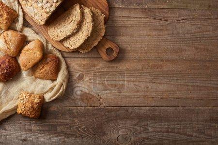 Foto de Vista superior de las rebanadas de pan fresco en la tabla de cortar y bollos en tela sobre la mesa de madera - Imagen libre de derechos