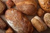 "Постер, картина, фотообои ""верхний вид на свежие домашние буханки хлеба и булочки на деревянном деревенском столе"""
