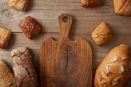 Photo for Top view of fresh homemade loaves of bread and buns near empty chopping board on wooden rustic table - Royalty Free Image
