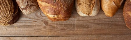 Photo for Top view of fresh homemade loaves of bread on wooden table, panoramic shot - Royalty Free Image