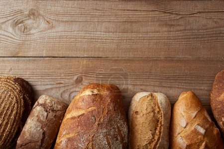 Photo for Top view of fresh homemade loaves of bread on wooden table with copy space - Royalty Free Image