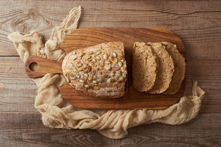 Photo for Top view of fresh homemade cut bread with seeds on wooden chopping board near cloth - Royalty Free Image