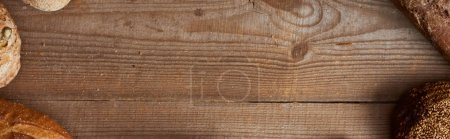 Photo for Top view of fresh homemade bread on wooden brown table with copy space, panoramic shot - Royalty Free Image