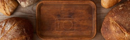 Photo for Panoramic shot of wooden chopping board among bread - Royalty Free Image