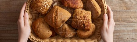 top view of woman holding fresh homemade buns in wicker basket above wooden table, panoramic shot