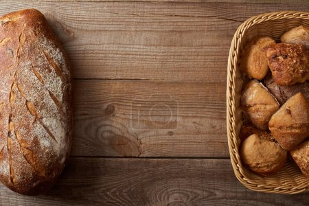 top view of wicker basket with buns and loaf of bread on wooden table