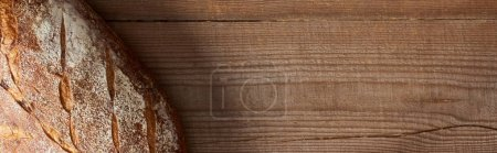 top view of fresh bread loaf on wooden table, panoramic shot