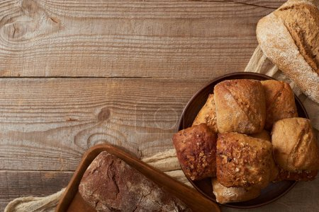 Photo for Top view of bread loaves and buns on rustic cloth on wooden table - Royalty Free Image