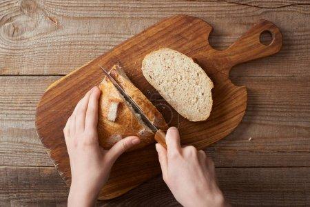 Foto de Vista parcial de la mujer cortando pan en tabla de cortar madera - Imagen libre de derechos