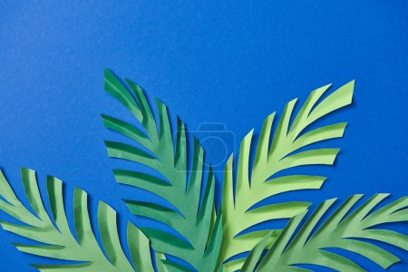 Photo for Top view of green paper cut leaves on blue background with copy space - Royalty Free Image