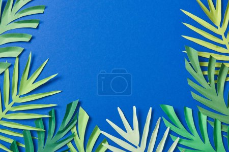 Photo for Top view of green paper cut tropical leaves on blue background with copy space - Royalty Free Image