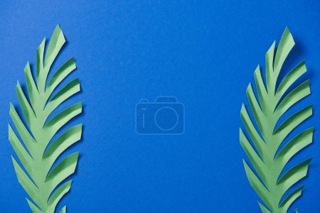 top view of green paper cut leaves on blue background with copy space