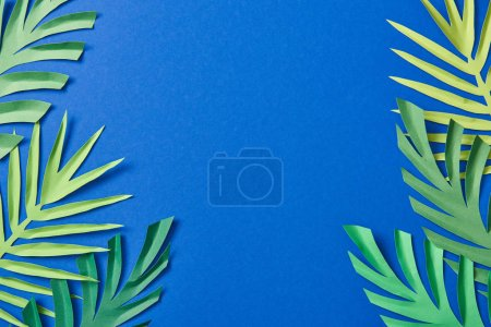 Photo for Top view of green paper cut exotic leaves on blue background with copy space - Royalty Free Image
