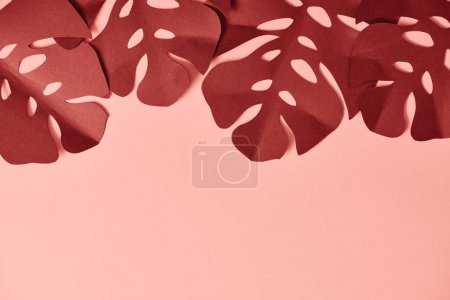 Photo for Top view of paper cut textured palm leaves on pink background - Royalty Free Image