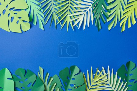 Photo for Top view of green exotic leaves on blue background with copy space - Royalty Free Image