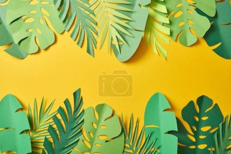 Photo pour Vue du dessus des feuilles de palmier vert découpées sur fond jaune avec espace de copie - image libre de droit
