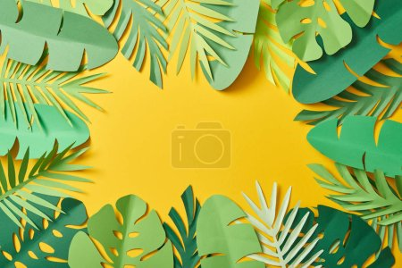 Photo for Top view of paper cut green palm leaves on yellow background with copy space - Royalty Free Image
