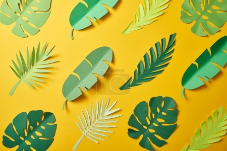 Foto de Vista superior de hojas de palma verde cortadas en papel sobre fondo amarillo, patrón sin costuras - Imagen libre de derechos