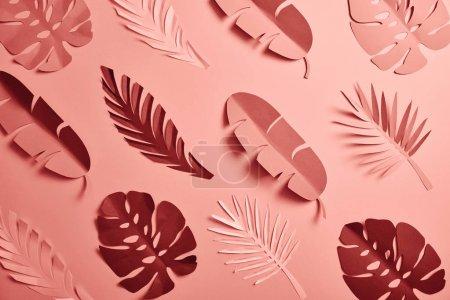 Photo pour Vue supérieure des feuilles de palmier coupées en papier sur le fond rose, modèle sans couture - image libre de droit