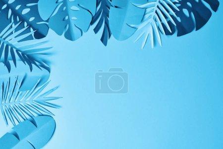 Photo pour Cadre de papier minimaliste bleu feuilles de palmier coupées sur fond bleu avec espace de copie - image libre de droit