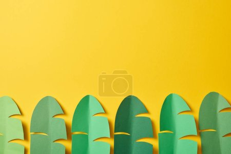 Photo pour Vue du haut des feuilles de palmier vert exotique découpées sur fond jaune avec espace de copie - image libre de droit