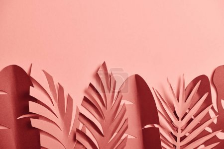 top view of decorative paper cut palm leaves on pink background with copy space