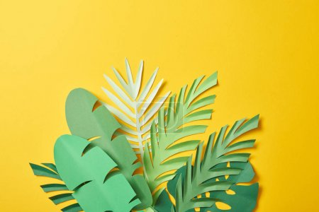 Photo for Bunch of paper cut exotic green palm leaves on yellow background with copy space - Royalty Free Image