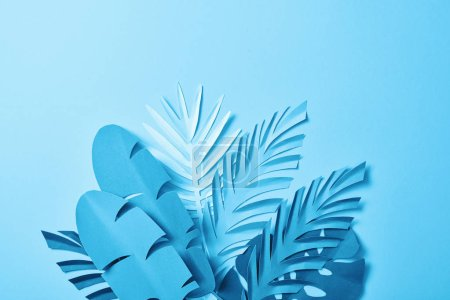 Photo for Bunch of blue minimalistic paper cut palm leaves on blue background with copy space - Royalty Free Image