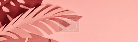 Photo for Panoramic shot of paper cut palm leaves on pink background - Royalty Free Image