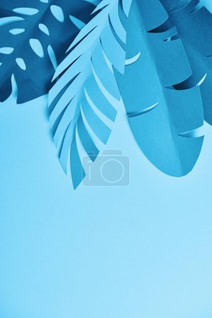 Photo for Top view of blue paper cut palm leaves on blue background with copy space - Royalty Free Image
