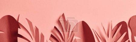 Foto de Foto panorámica de hojas de palma decorativas de corte de papel sobre fondo rosa - Imagen libre de derechos