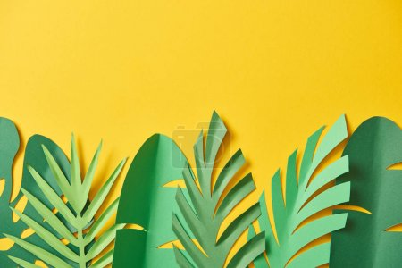 Photo for Top view of paper cut exotic green palm leaves on yellow background with copy space - Royalty Free Image