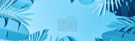 Photo for Frame of blue minimalistic paper cut palm leaves on blue background with copy space - Royalty Free Image
