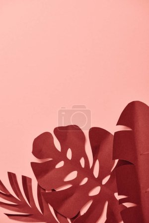 Photo for Top view of paper cut burgundy palm leaves on pink background with copy space - Royalty Free Image