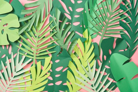 top view of scattered green palm leaves on pink background with copy space