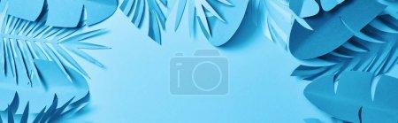Photo pour Vue du haut des feuilles de palmier bleu minimaliste en papier coupé sur fond bleu avec espace de copie, vue panoramique - image libre de droit