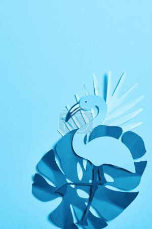 Photo for Top view of blue minimalistic paper cut palm leaves and flamingo on blue background with copy space - Royalty Free Image