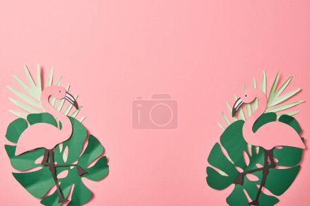 Photo for Top view of paper cut flamingos on green palm leaves on pink background with copy space - Royalty Free Image