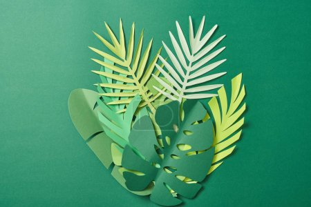 Photo for Top view of tropical paper cut palm leaves on green background with copy space - Royalty Free Image