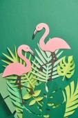 """Постер, картина, фотообои """"верхний вид экзотической бумаги вырезать пальмовые листья и розовые фламинго на зеленом фоне с копией пространства"""""""