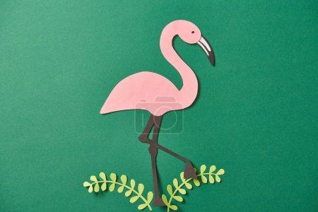 Foto de Vista superior de las hojas cortadas en papel y el flamenco rosa sobre fondo verde - Imagen libre de derechos