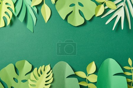 Photo for Top view of exotic paper cut palm leaves on green background with copy space - Royalty Free Image