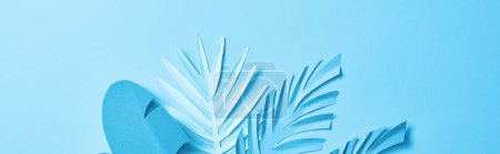 Photo for Top view of blue exotic paper cut palm leaves on blue background with copy space, panoramic shot - Royalty Free Image