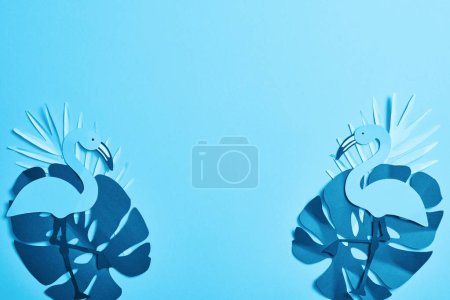 Photo for Top view of blue exotic paper cut palm leaves and flamingos on blue background with copy space - Royalty Free Image