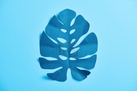 Photo for Top view of blue exotic paper cut palm leaf on blue background with copy space - Royalty Free Image