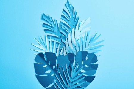 Photo for Top view of blue exotic paper cut palm leaves on blue background with copy space - Royalty Free Image