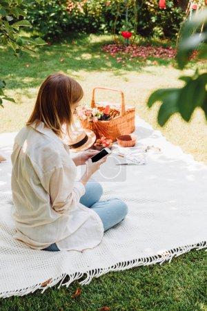 Foto de Chica rubia sentada en la manta en el jardín y tener picnic en el día soleado mientras se utiliza el teléfono inteligente - Imagen libre de derechos