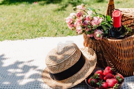 Photo pour Panier en osier avec roses et bouteille de vin sur couverture blanche près du chapeau de paille et des fraises lors d'une journée ensoleillée dans le jardin - image libre de droit